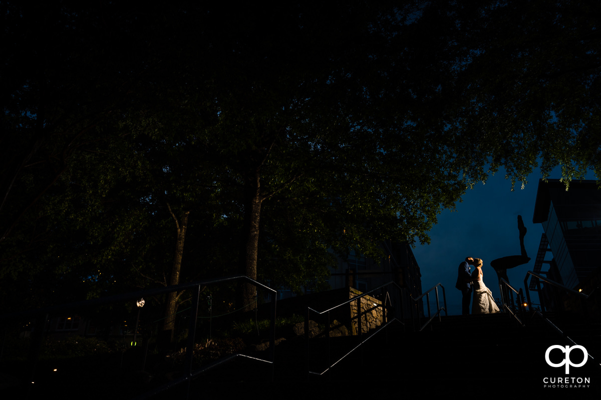 Groom kissing his bride at the top of steps leading into Falls Park after their Mary's at Falls Cottage wedding in downtown Greenville,SC.