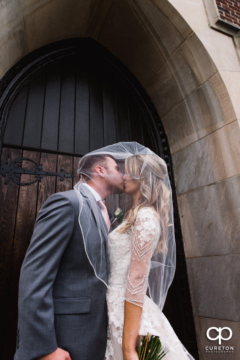 Groom kissing his bride underneath her veil in front of a church in Greenville.