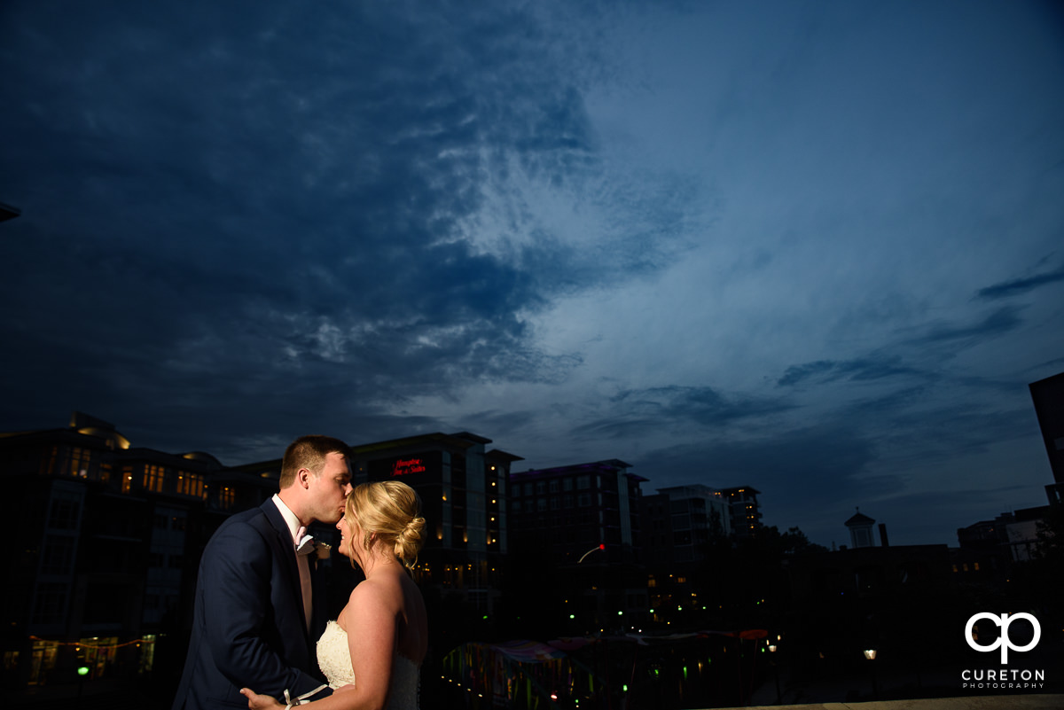 Groom kissing his bride on the forehead in front of the skyline at night after their Mary's at Falls Cottage wedding in downtown Greenville,SC.