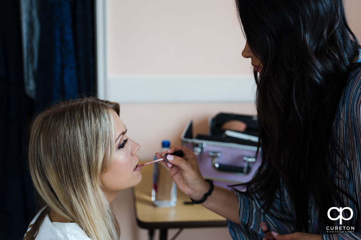 Courtney Gray applying makeup to the bride.