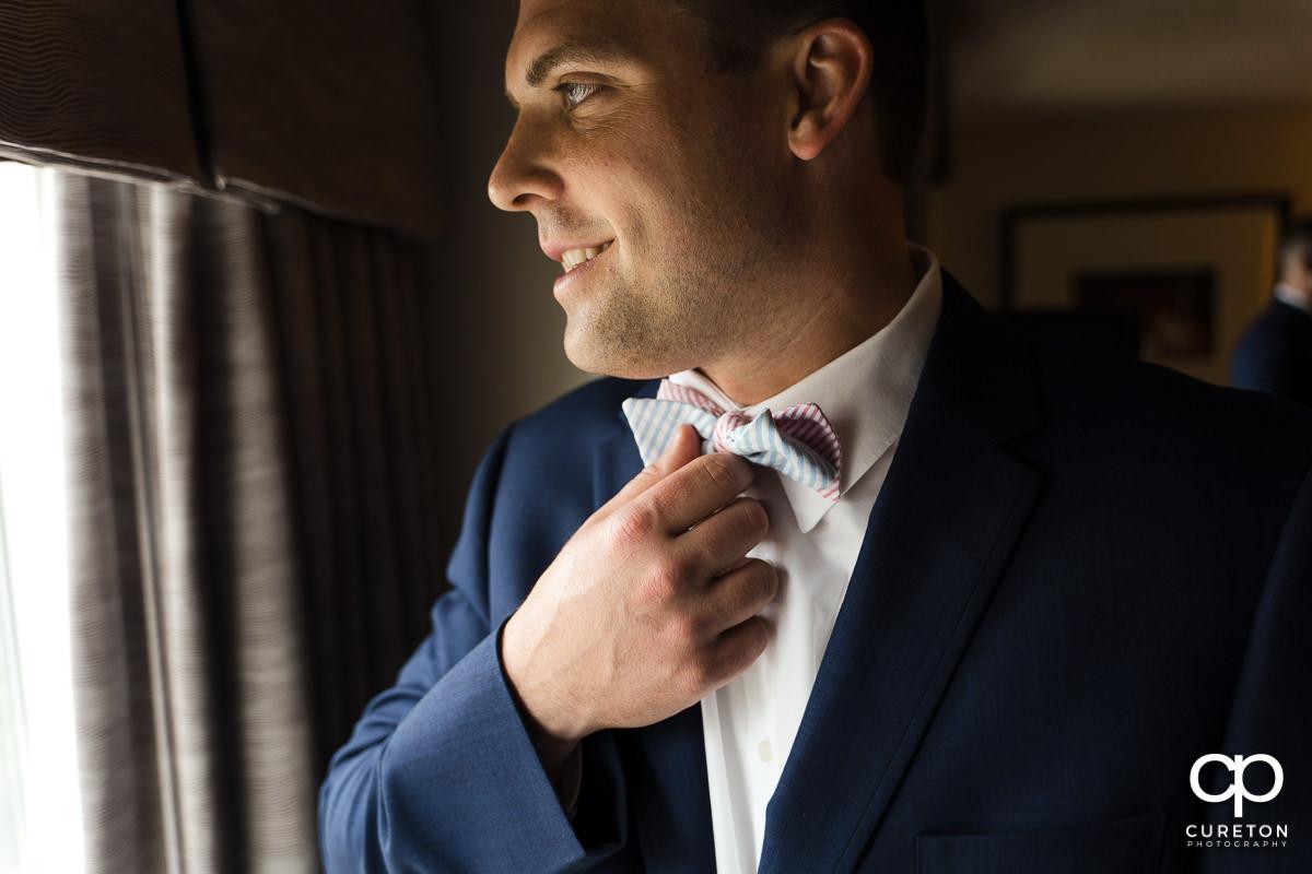 Groom adjusting his bow tie.