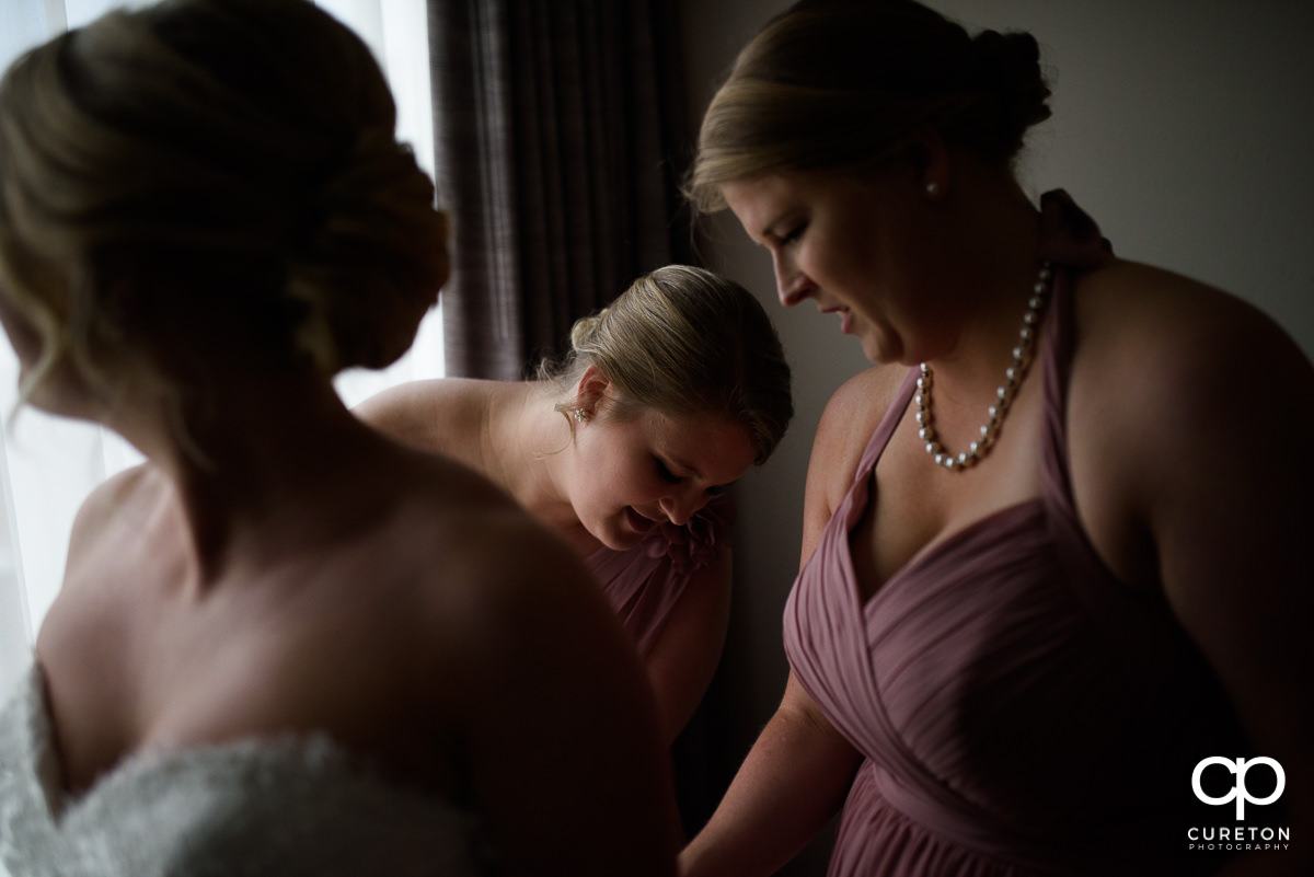 Bride's sisters helping her button her dress.