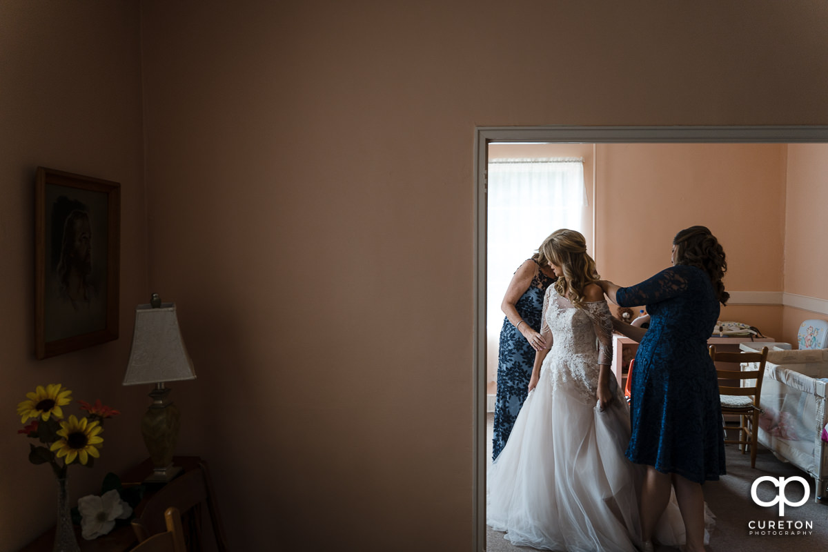 Bride being helped into her dress by her mother and sister.