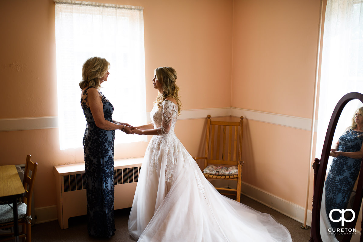 Bride and her mother holding hands before the ceremony.
