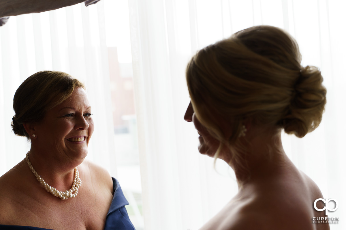 Bride's mom looking at her as they get ready for the wedding ceremony.