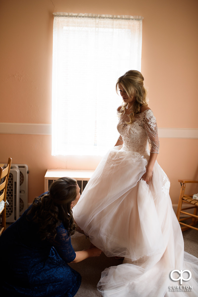 Bride's sister putting her shoes on.