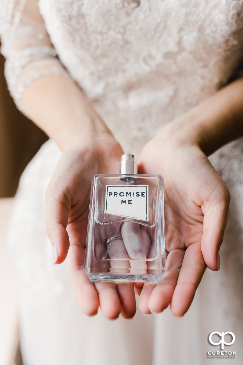 Bride holding a bottle of Promise Me perfume.