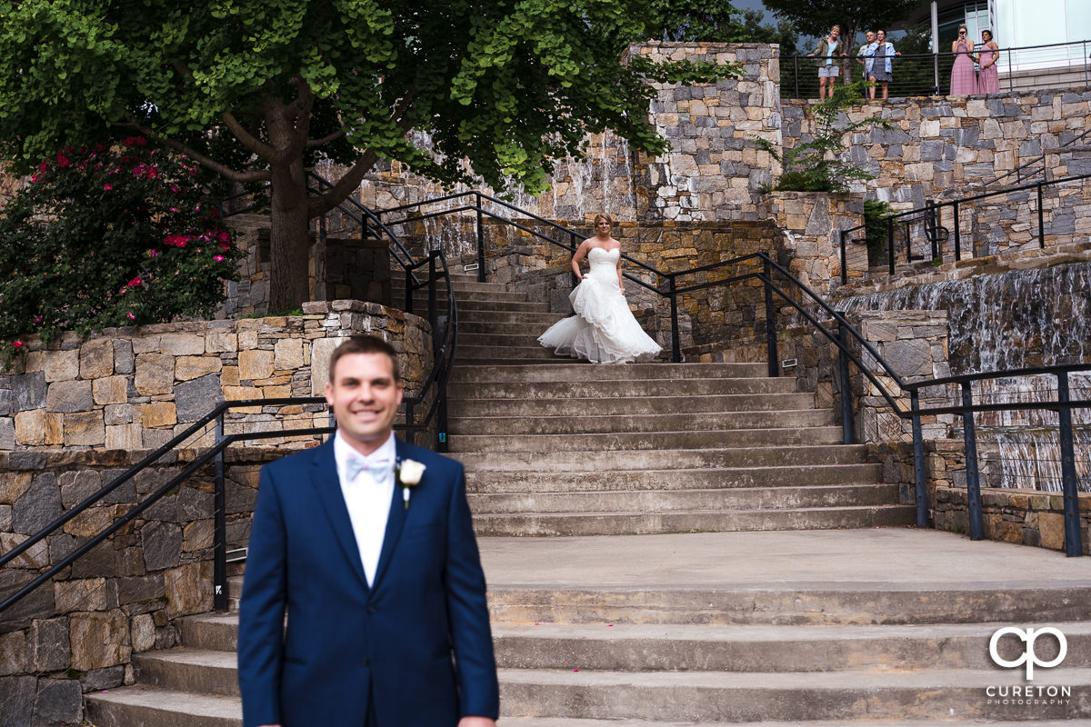 Bride walking down some steps for a pre-wedding first look in downtown Greenville.