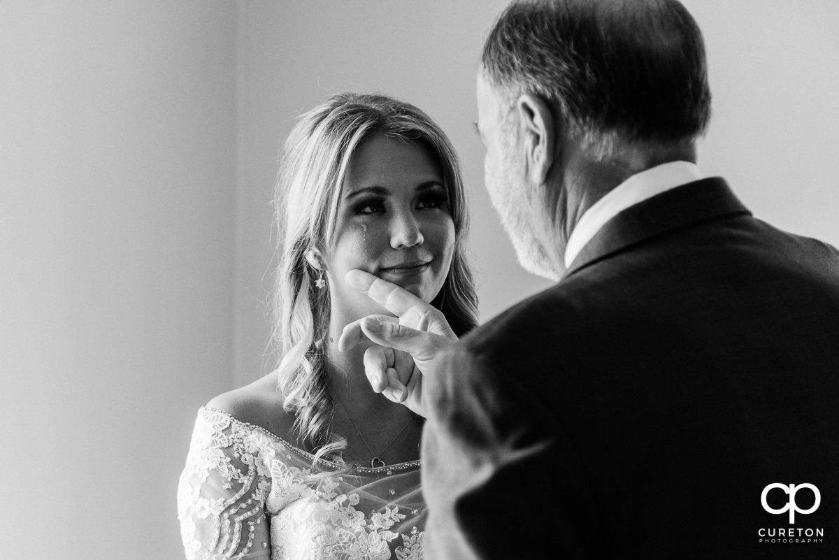 Bride's father wiping a tear from her face as they share a moment before her wedding.