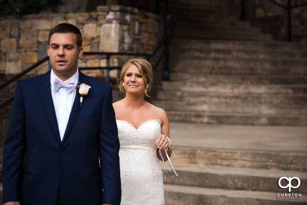 Bride tearing up as she walks up to her groom at a pre-wedding first look in downtown Greenville.