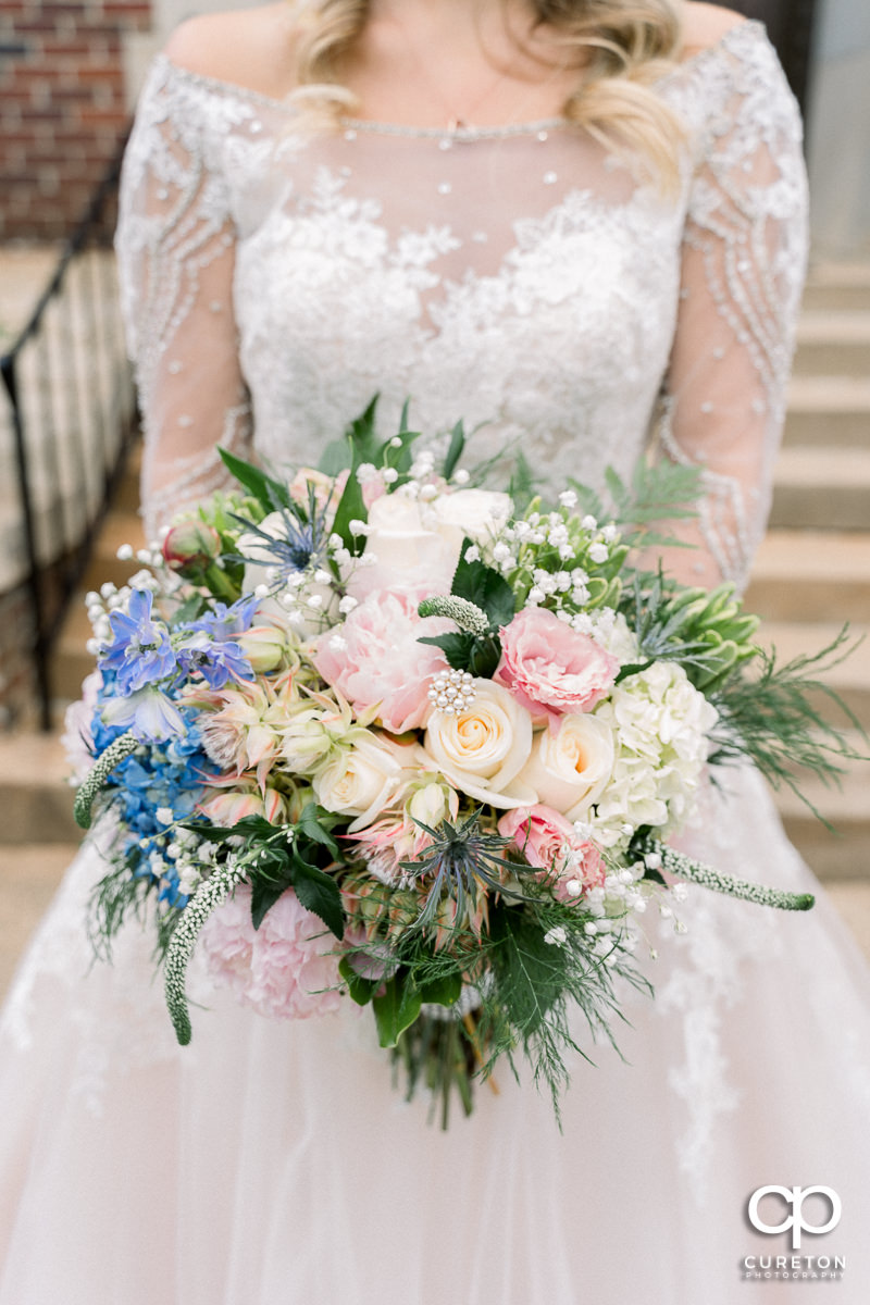 Bride holding a gorgeous bouquet .