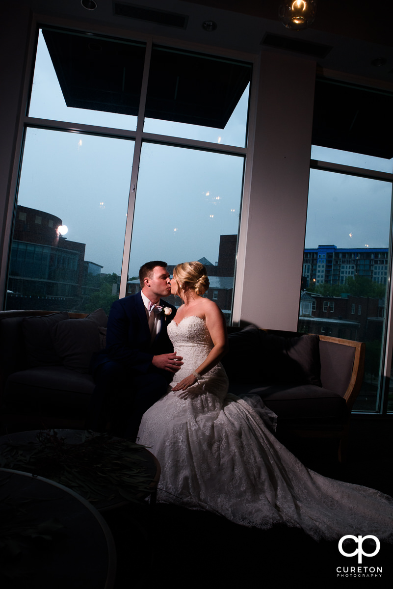 Bride and groom kissing inside Nose Dive restaurant in Greenville,SC before their wedding.