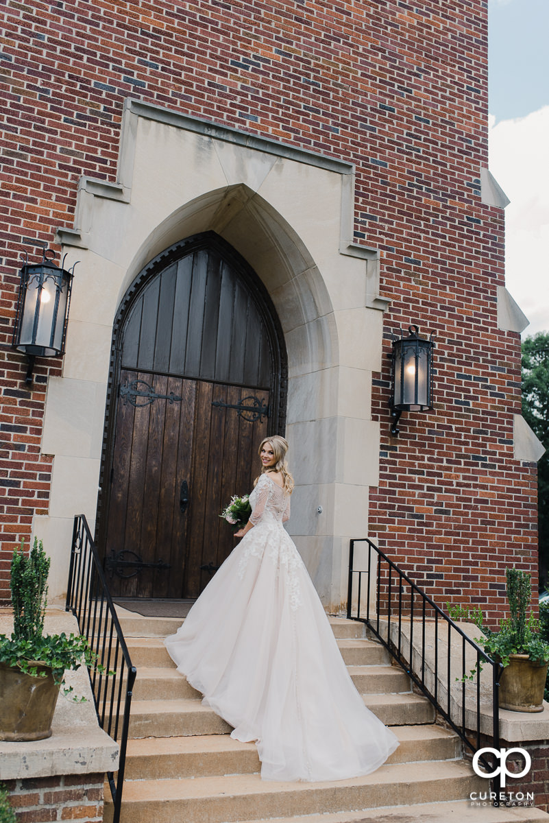 Bride showing off the back of her dress on the steps of the church.