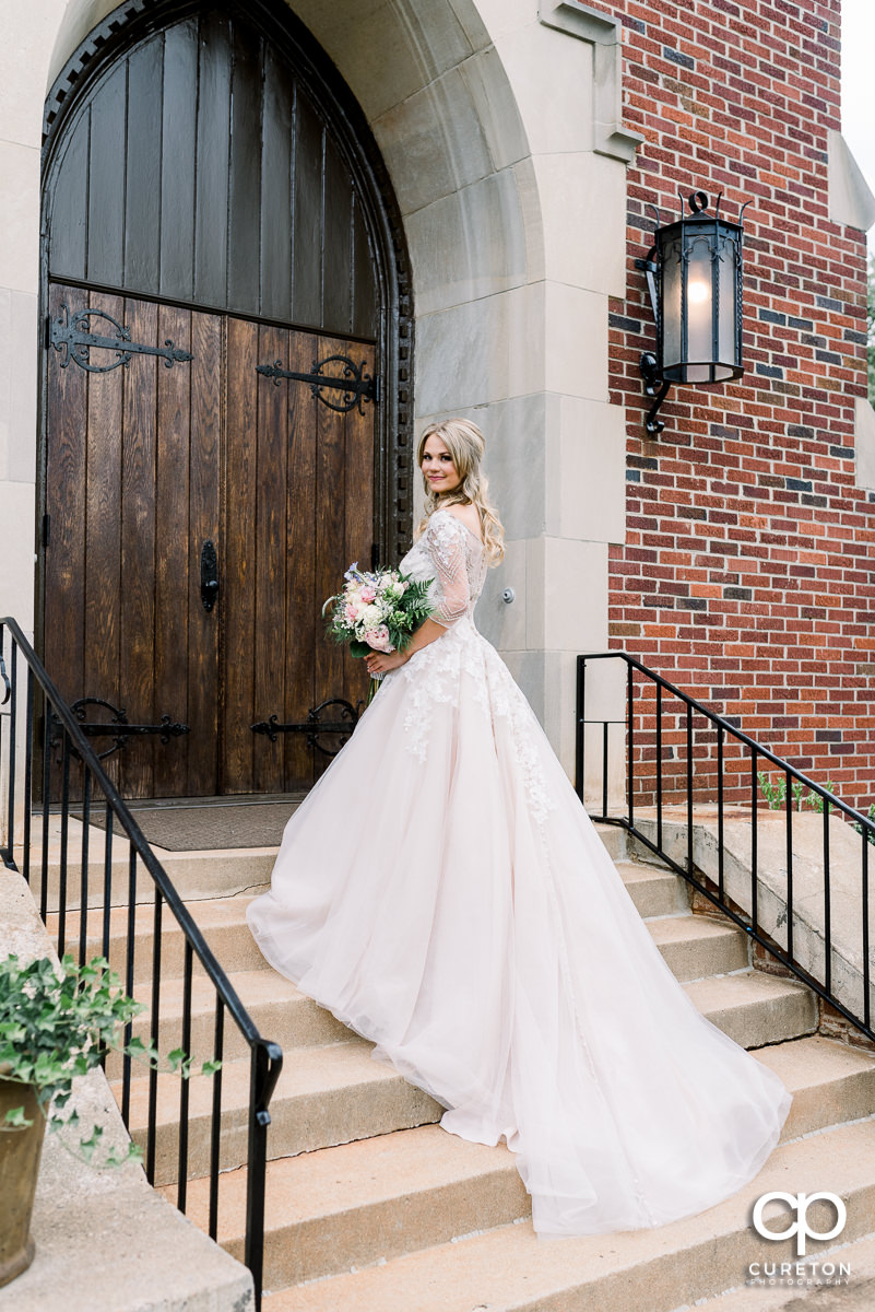 Bride holding her flowers on the steps of the church in Greenville.