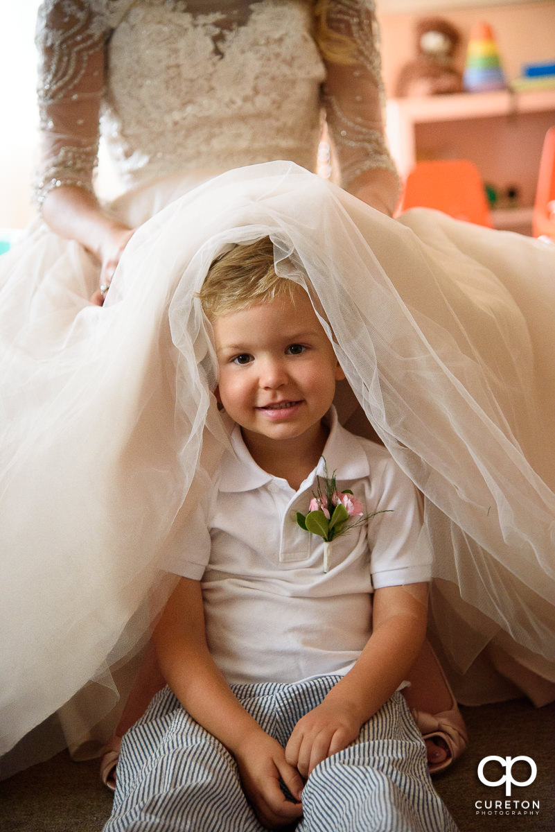 Bride's nephew hiding underneath her dress.
