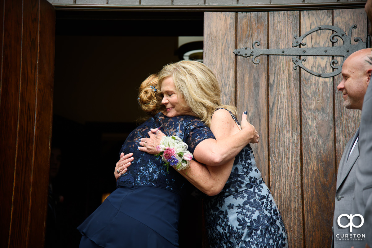 Bride's mother hugging the groom's mom.