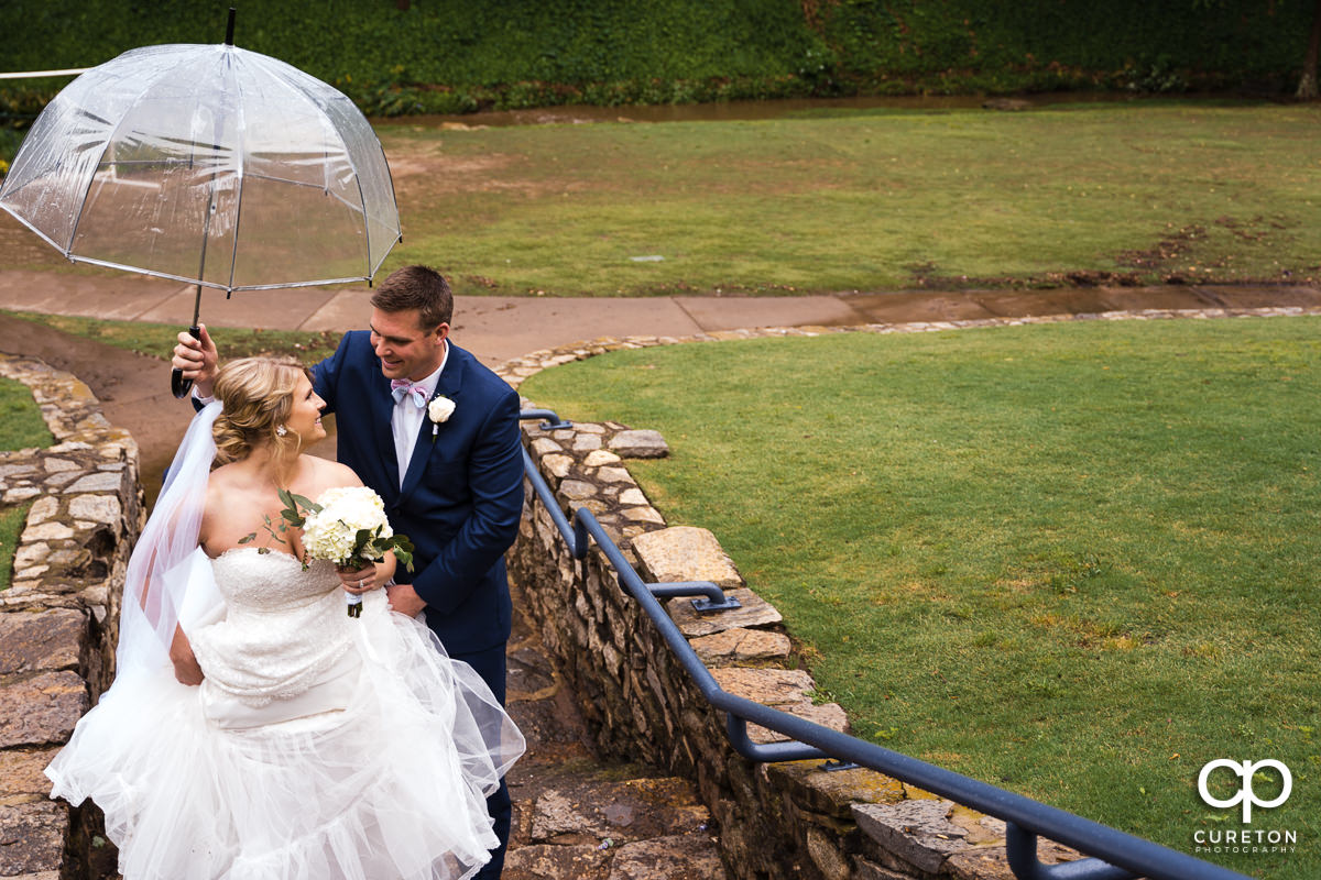 Bride and groom walking up some steps in Falls Park in the rain.