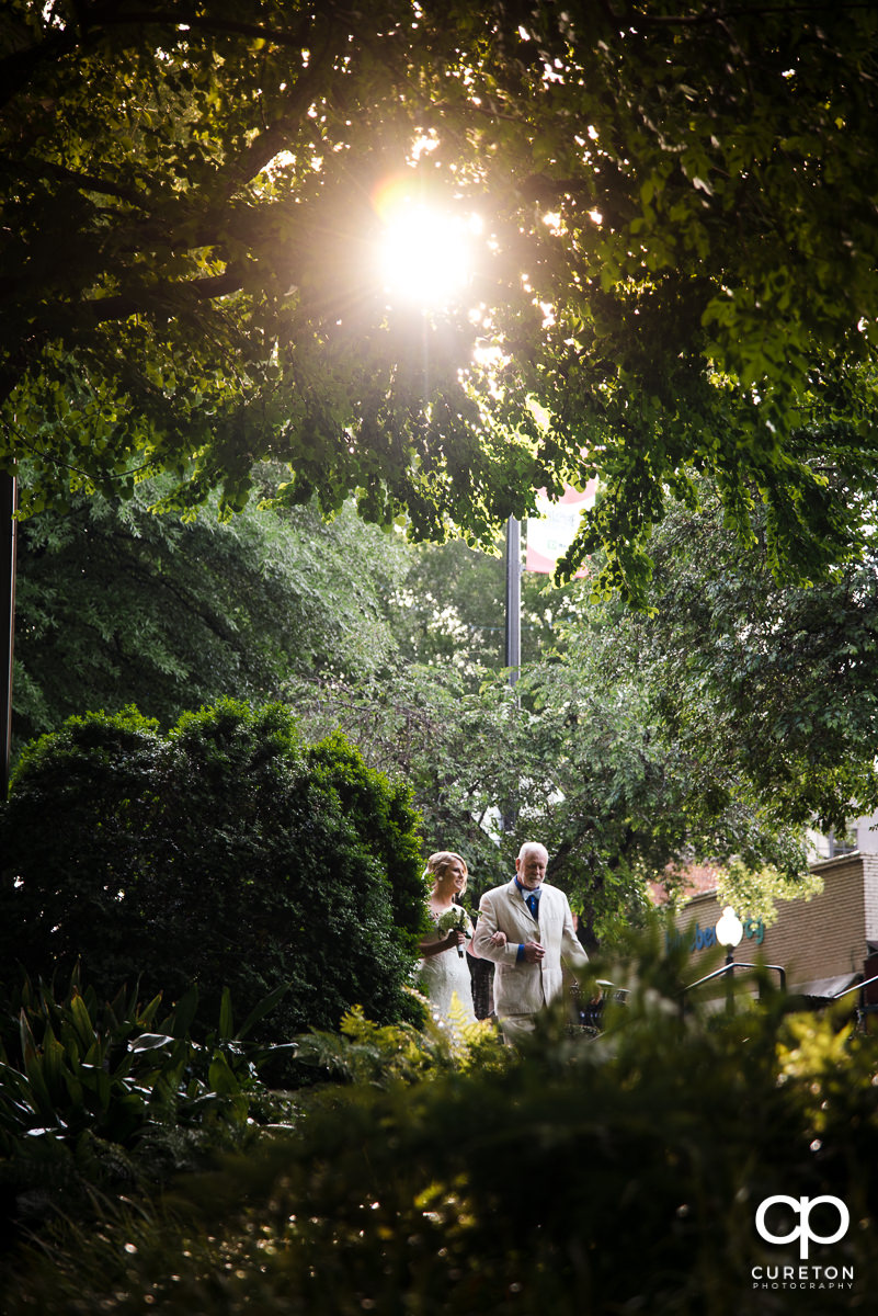Bride and her father walking down the aisle at the Mary's at Falls Cottage wedding in downtown Greenville,SC.