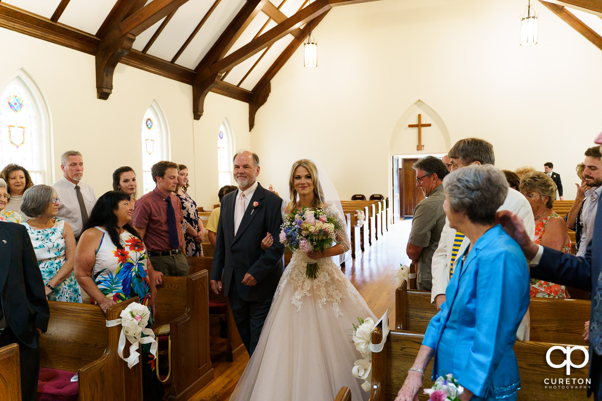 Bride and her dad walking down the aisle.