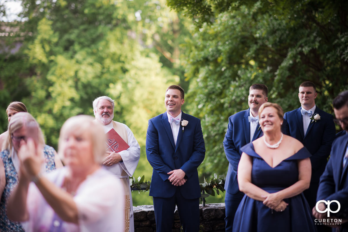Groom sees his bride walking down the aisle at the Mary's at Falls Cottage wedding in downtown Greenville,SC.