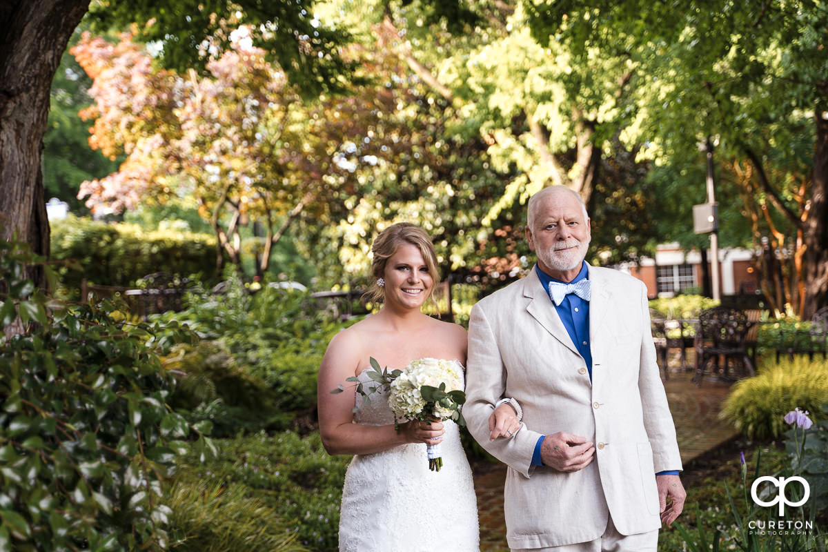 Bride being walked down the aisle by her father at the Mary's at Falls Cottage wedding in downtown Greenville,SC.