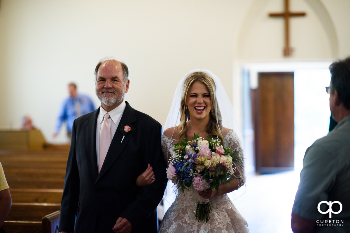Bride laughing and smiling as she is walked down the aisle on her wedding day in Greenville,SC.