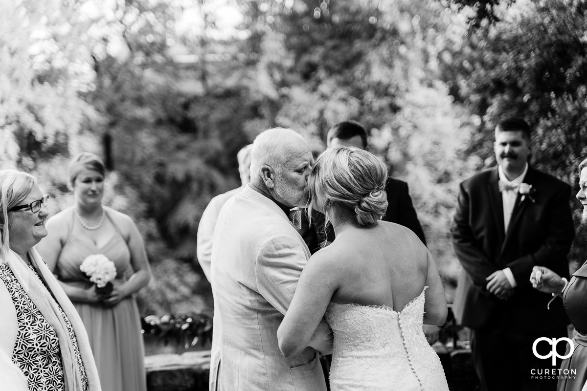 Bride's father giving away his daughter at the ceremony.