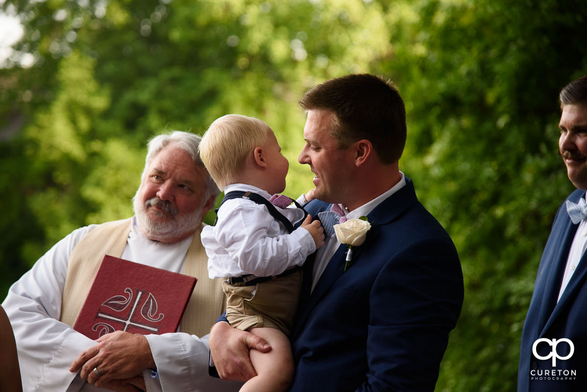Groom holding his son during the ceremony.