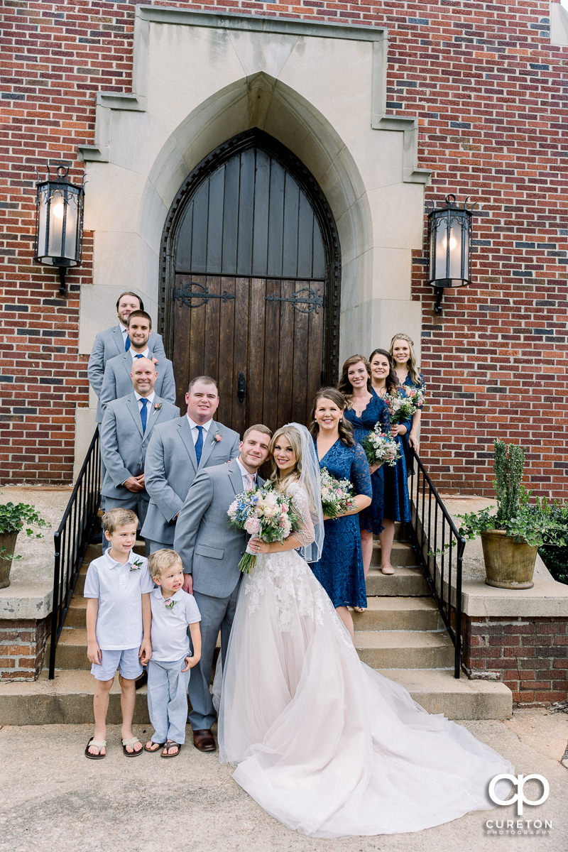 Wedding party standing on the steps of the church.