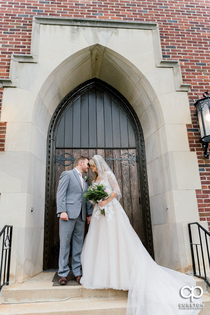Bride and groom leaning into each other on the steps of the church.