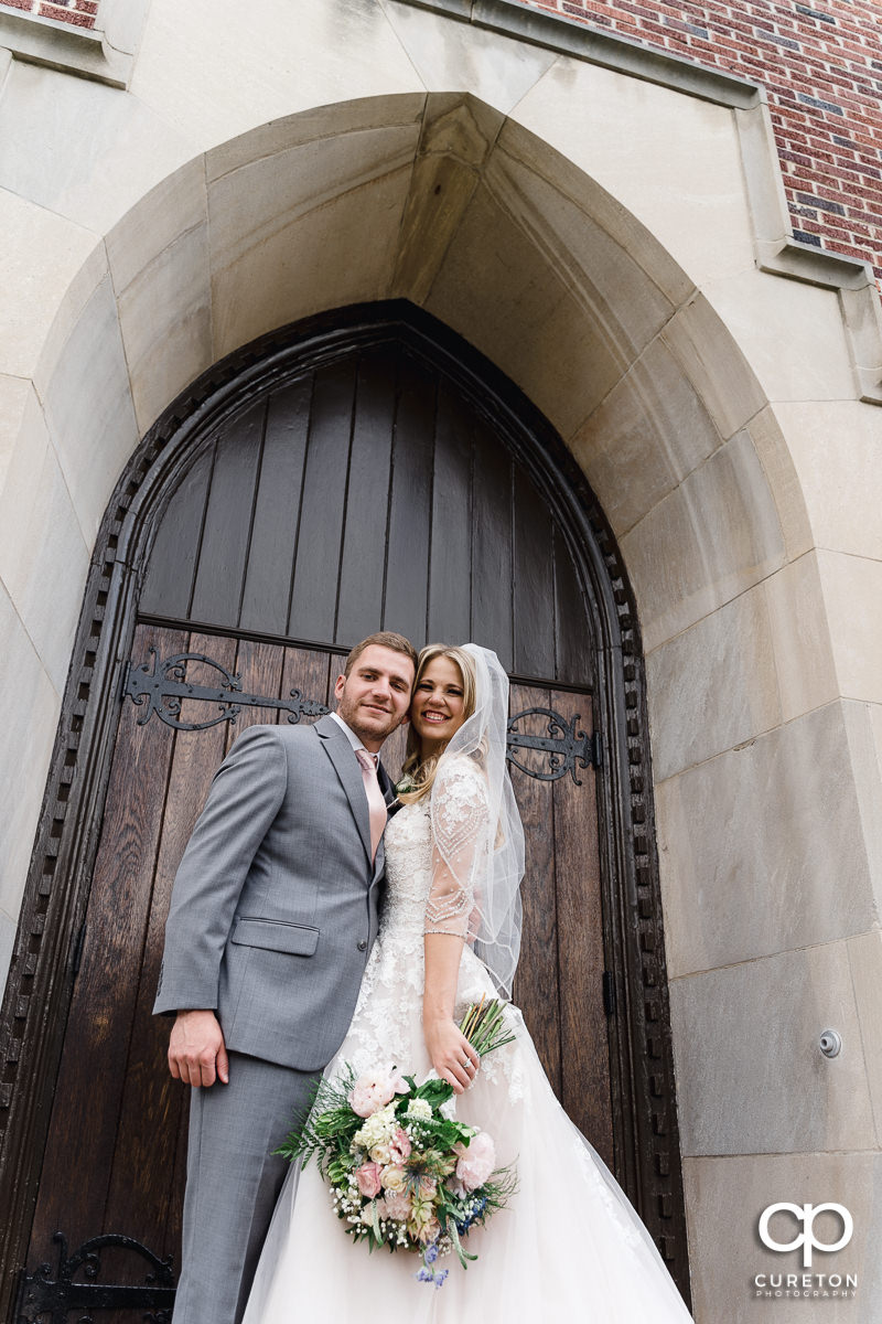 Bride and groom on the steps of the church.