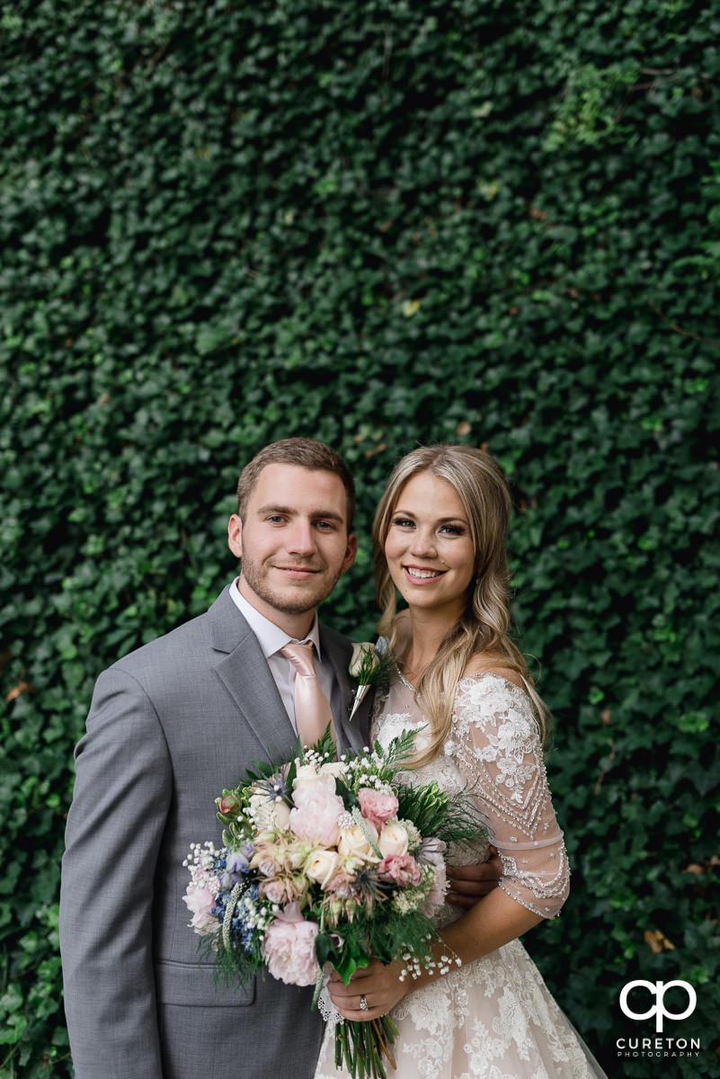 Bride and groom walking in front of an ivy wall after their Falls Park wedding at Mary's cottage in downtown Greenville,SC.