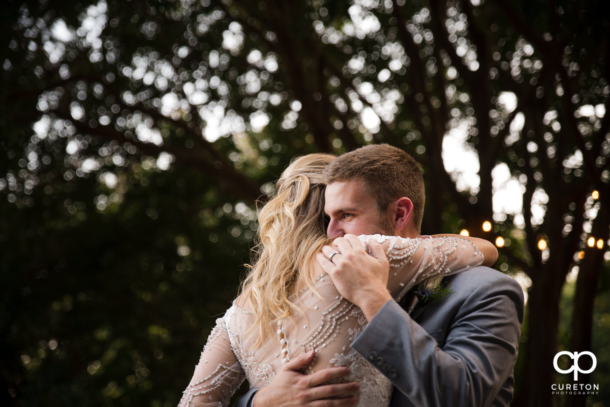 Groom hugging his bride as they dance at their wedding reception at Mary's cottage at Falls Park in downtown Greenville,SC.