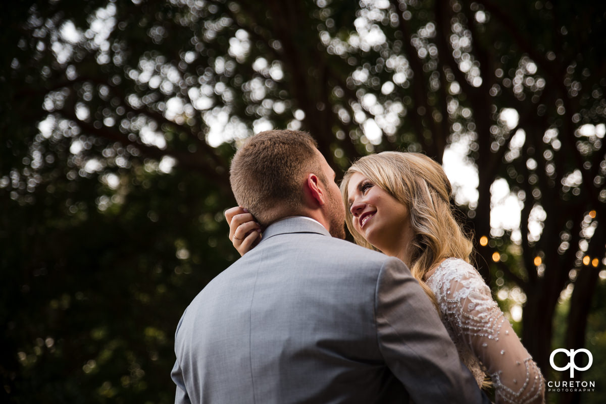 Bride gazing into her husbands eyes as they dance at their wedding reception at Mary's cottage at Falls Park in downtown Greenville,SC.