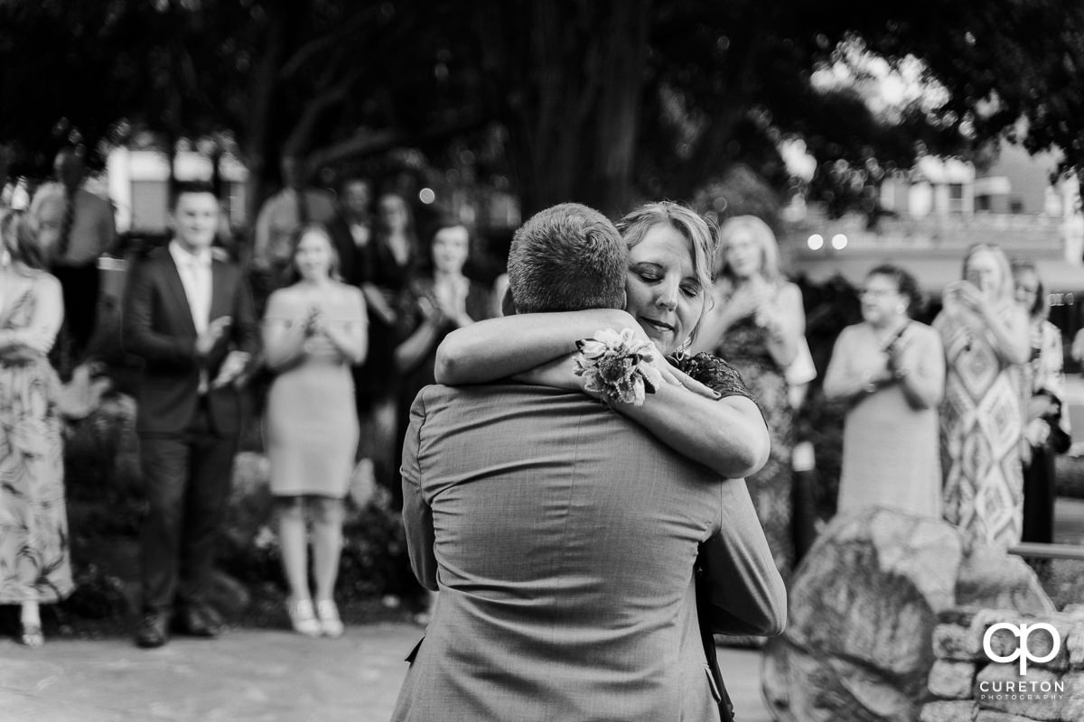Groom hugging his mother after they shared a dance at his wedding reception.