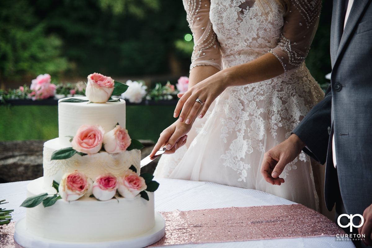 Bride and groom cutting the cake at their wedding.
