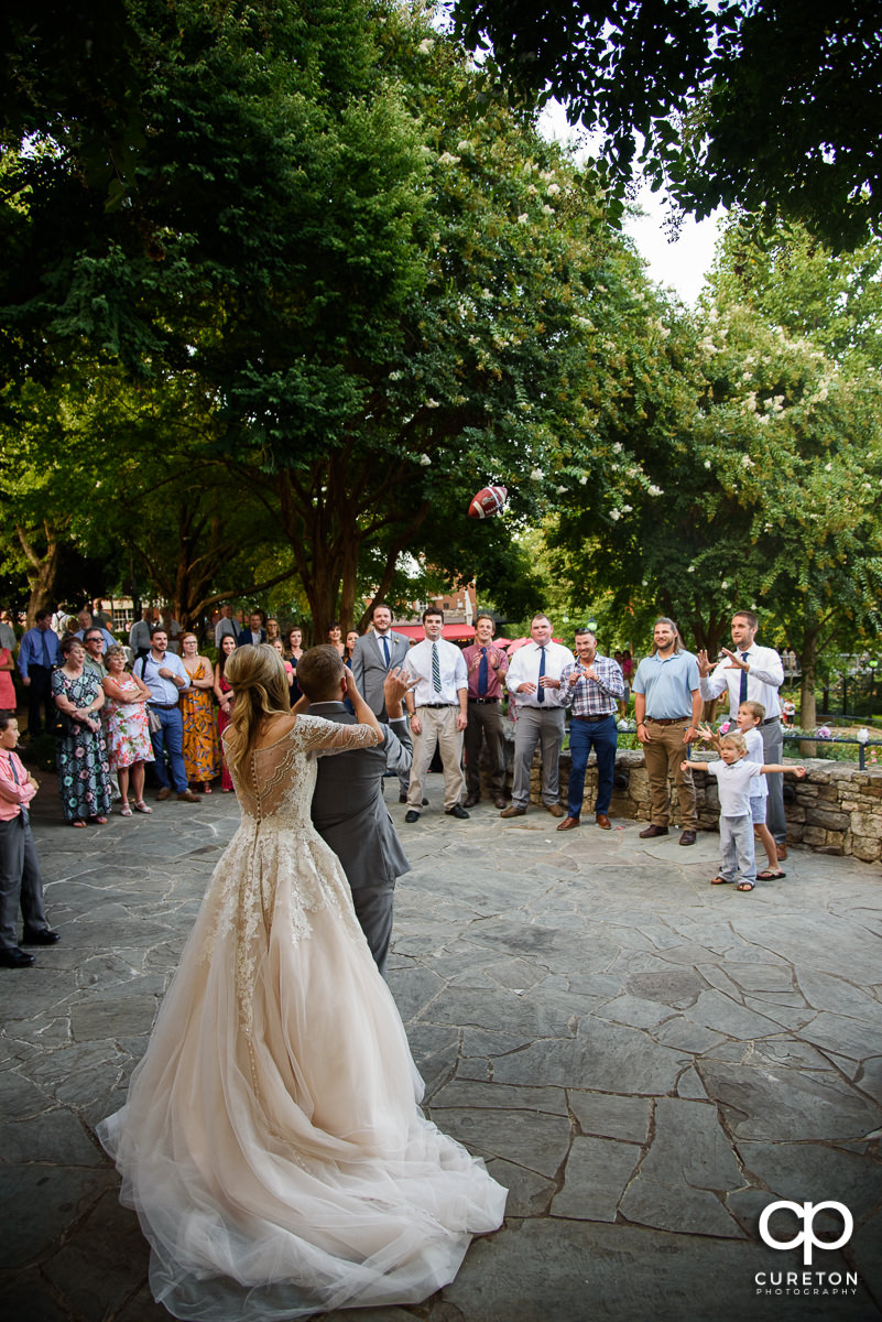 Groom tossing the garter on a football.