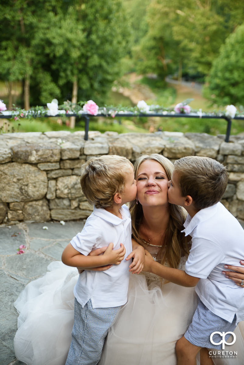 Ring bearers kissing the bride on the cheek.