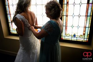 Bride's mom helping her into the dress.