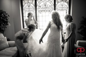 Bride's mom and sisters help her get ready.
