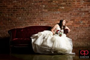 Bride laughing on a vintage couch.