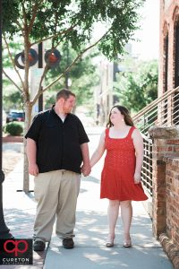 Engaged couple walking down Main St in downtown Greenville,SC.