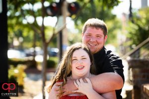 Couple hugging in front of the Old Cigar Warehouse in downtown Greenville SC.