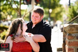 Engaged couple looking at each other in downtown Greenville.