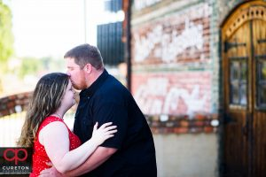 Groom kissing his future bride on the forehead.