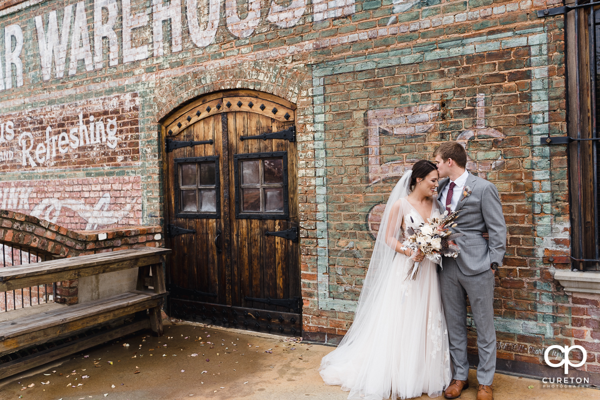 Groom kissing his bride on the forehead before their fall wedding at The Old Cigar Warehouse in Greenville,SC.