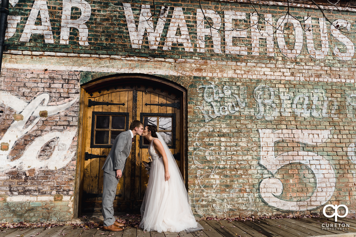 Bride and groom kissing in a doorway on the back deck after their wedding ceremony at The Old Cigar Warehouse in Greenville,SC.
