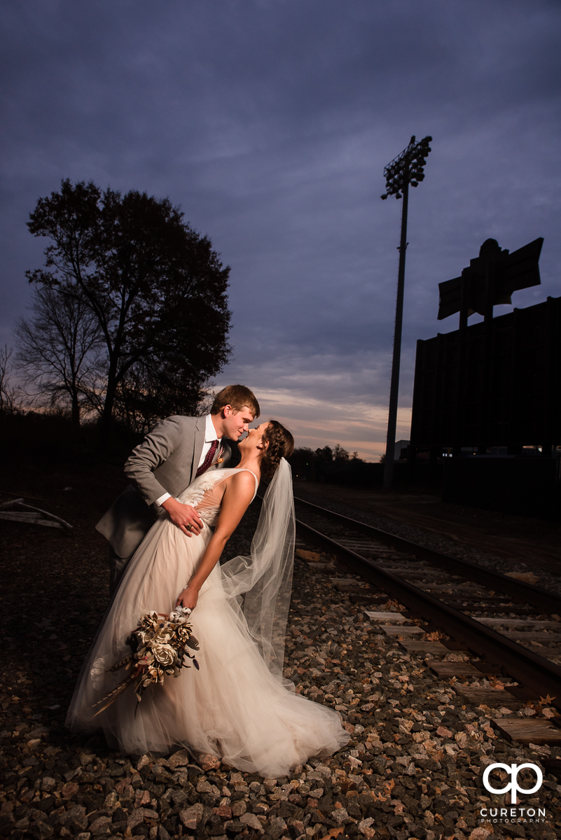 Groom dipping his bride at sunset at their wedding ceremony at The Old Cigar Warehouse in Greenville,SC.