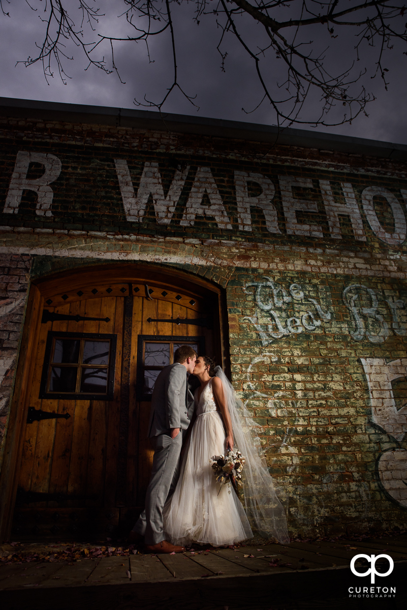Bride and groom kissing at night on the back deck of The Old Cigar Warehouse.