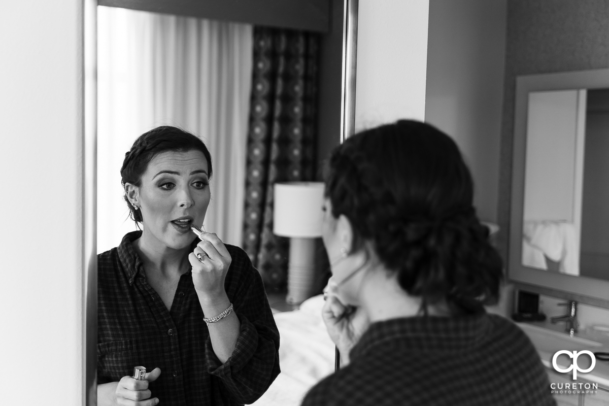 Bride putting makeup on.
